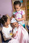 Education Preschool classroom scenes 3 year olds two girls and boy playing scene with boy as the baby fed by one of the girls as the other puts a cap on his head