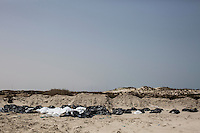 The bodies of dead migrants, collected from the Zuwara shore by a vigilante group, are lined up for burial at an improvised graveyard in Abu Kammash, west Libya.