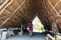 A visitor walks through a traditional thatched Hawaiian hale at Pu'uhonua o Honaunau, or City of Refuge, Big Island of Hawai'i.