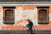 Antigua, Guatemala.  Old Man on Bicycle Rides Past an Old House with Flaking Paint.