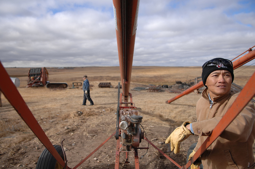 Sheldon Zou inspects a grain auger at a farm auction near Ogema, Saskatchewan, Canada. Zou immigrated from China to Ogema in 2008. Zou, his wife Linda and daughters Jennifer and Angela now own over 4,000 acres of land in the tiny community 115 kilometres south of Regina. MARK TAYLOR FOR THE GLOBE AND MAIL.
