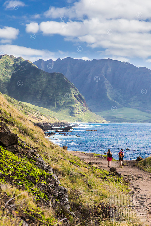 Two women take in the view as they hike along Ka'ena Point Trail, with Yokohama Bay and Makua Valley in the distance, West O'ahu.