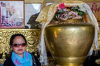 Nepal, Kathmandu, Swayambhunath.  Woman Visiting Buddha Shrine.  Cash Donations above Urn.