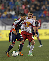 New England Revolution midfielder Lee Nguyen (24) dribbles as New York Red Bulls midfielder Eric Alexander (12) pressures. In a Major League Soccer (MLS) match, the New England Revolution (blue) tied New York Red Bulls (white), 1-1, at Gillette Stadium on May 11, 2013.