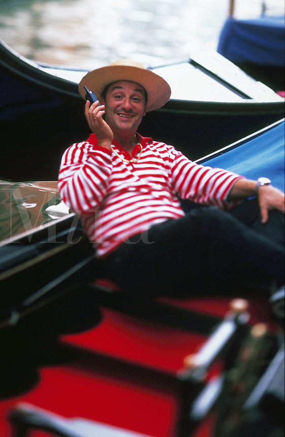 Portrait of a smiling gondolier in traditional uniform. Venice, Italy.