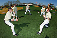 Wake Forest Demon Deacons Kevin Conway (left) and Eric Ramsey (right) concentrate on catching the baseballs as teammates Conor Keniry (14), Evan Stephens (5) and Joey Rodriguez (7) look on prior to the game against the Virginia Cavaliers at Wake Forest Baseball Park on April 6, 2013 in Winston-Salem, North Carolina.  (Brian Westerholt/Four Seam Images)