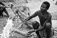 A Hadza man heats a stick in order to make it more pliable, so he can form it into an arrow.