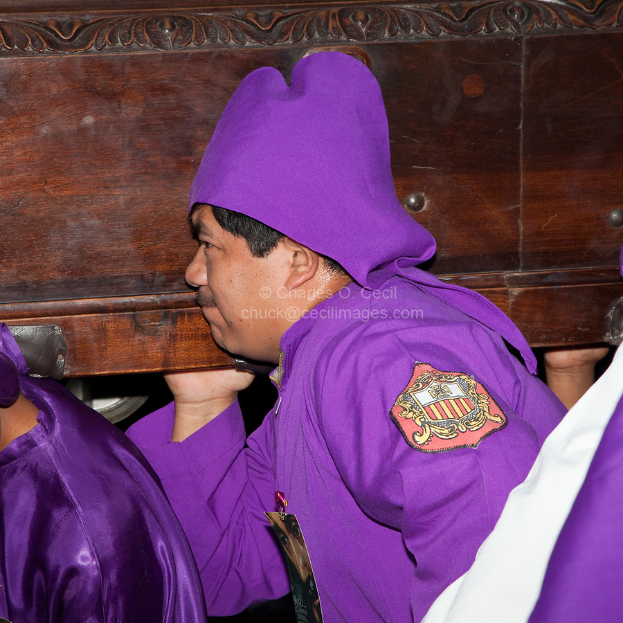 Antigua, Guatemala.  A Cucurucho Carrying a Float (Anda) in a Religious Procession during Holy Week, La Semana Santa.