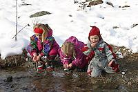 Kinder trinken im Winter kristallklares Gebirgswasser direkt aus dem Bach