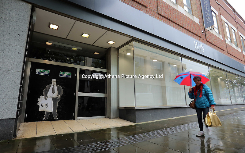 """Pictured: A woman walks past a poster of Sir Philip Green on the door of the now closed down BHS store in Oxford Street, Swansea, Wales, UK. Tuesday 13 September 2016<br /> Re: Former owner of BHS, Sir Philip Green has paid a surprise 'visit' to the closed down BHS store in Swansea.<br /> He was spotted in the doorway of the Oxford Street store, which closed its doors for the last time last month.<br /> In his hand was a BHS shopping bag with money spilling out of it.<br /> Sir Philip had owned BHS before selling it for £1 last year.<br /> He is claimed to have taken millions out of the company in dividends and left behind a £571m pensions deficit.<br /> Alongside the poster are the words: """"Thankyou for your custom Sir""""."""