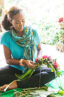 A Hawaiian cultural practitioner weaves a kupe'e (a wrist or ankle adornment) out of red 'ohi'a lehua flowers and fern leaves, Volcano, Hawai'i Island.