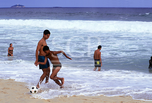 Itaparica Island, Bahia state, Brazil; boys playing football in the surf at the water's edge of a beach.