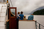 A family heads outbound during stormy weather on the vessel M.V. Frances Barkley, a historic freighter, formerly a Norwegian vessel, still in service on Albernie Inlet, British Columbia, Canada.