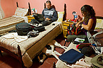 Andean Mountain Cat (Leopardus jacobita) biologists, Cintia Tellaeche and Juan Reppucci, relaxing in hotel room before heading into the field, Abra Pampa, Andes, northwestern Argentina