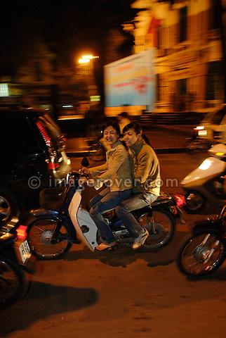 Asia, Vietnam, Hanoi. Hanoi old quarter. Two girls on motorbike on Le Thai To St.