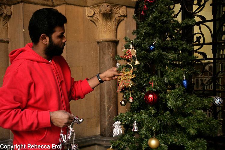 A Sri Lankan refugee dressing the Christmas tree at the Crimean Church, Istanbul, Turkey
