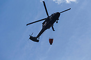 The silhouette of a Black Hawk helicopter with hanging water bucket flying over forest fire on Dilly Cliff in Kinsman Notch, New Hampshire in October 2017. These cliffs are located behind the Lost River Gorge and Boulder Caves on Route 112 in North Woodstock.