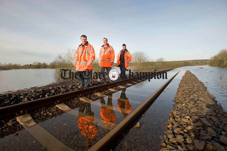Iarnroid Eireann Maintenance Crew Kevin Barry, Shane Moylan and Kevin O'Connor examine of a section of flooded tracks between Ennis and Limerick at Ballycar.Pic Arthur Ellis.
