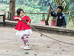 Young Lao girl struggles to pull a chain for some unknown reason.
