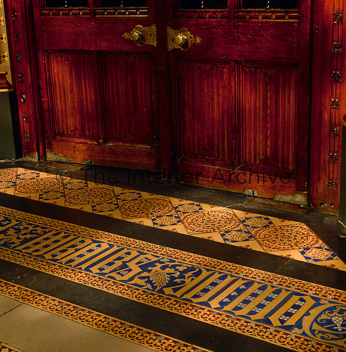 Detail of the tiled floor outside one of the chambers, decorated with gothic lettering and a fleur-de-lis motif