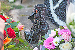 A decorated leather boot sitting with floral tributes to Keith Flint in the church grounds after the funeral of the late Prodigy singer at St Marys Church in Bocking,  Essex today.