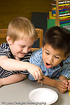 Preschool 3 year olds class pet hermit crab two boys playing with it vertical