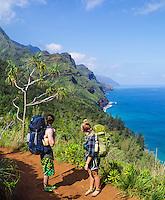 Two backpackers pause to look at the coastline on the Kalalau Trail on Kaua'i.