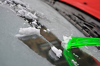 Scraping frost off of a car windscreen.
