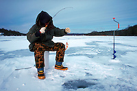 Man ice fishing with little fish