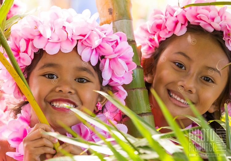 Girls wearing pink plumeria lei and haku head lei pose amid palm trees before a hula performance in Halei'wa, North Shore, O'ahu.
