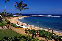 Beachgoers stroll along Kauai's Poipu Beach beneath palm trees along the ocean's edge