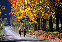 Fall scene. Two people walk together along a lonely country road in rural Virginia surrounded by autumn folliage. Abingdon Virginia.