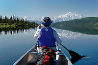 A woman paddles a canoe in the middle of Wonder Lake on a crystal clear and calm summer day.  A mirror relfection of Mt. McKinley makes this a special moment in Denali National Park.