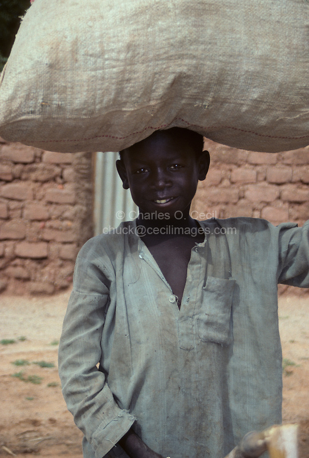 Saouanaoua, Niger, West Africa.  Hausa Village Boy with Sack on Head.