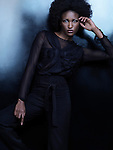 Beautiful african american woman wearing fashionable black clothes posing on shiny black background. High fashion photo. Image © MaximImages, License at https://www.maximimages.com