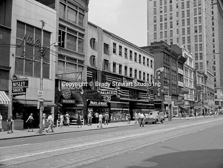 Pittsburgh PA:  View east on Liberty Avenue toward Pennsylvania Railroad Station.  Businesses on the north side (600 block) of the street include Nisley Shoes, Wilkens Jewelers, Palace Jewelers, Armor Modern Kitchens, Carnegie Park Mens store, Isalys Deli, Kings Clothing Store, Lomakin Music, Robert's Restaurant & Bar, Pettey Musical Instruments, and Western Union.