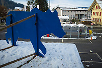 Switzerland. Canton Bern. Bärau. Winter time. A wooden blue bear sculpture. A woman stands up at a bus stop waiting for the bus to arrive. Snow on roofs. Protection for bird from hitting glass. Sticker of bird predator glued on glass window. Collision prevent. Bärau is a village in the municipality of Langnau in Emmental in the administrative district of Emmental in the canton of Bern.14.12.2020 © 2020 Didier Ruef
