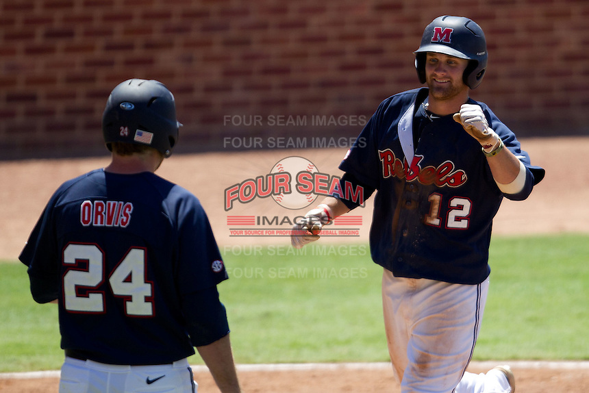 Outfielder Tanner Mathis #12 of the Ole Miss Rebels is greeted by teammate Sikes Orvis #24 during the NCAA Regional baseball game against the Texas Christian University Horned Frogs on June 1, 2012 at Blue Bell Park in College Station, Texas. Ole Miss defeated TCU 6-2. (Andrew Woolley/Four Seam Images).