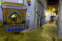 Chefchaouen, Morocco.  Young Boy Drinking at Public Water Tap in the Medina at Night.