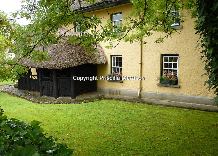 Adare, Ireland - July 18, 2010:  A thatch-roofed structure is attached to a larger building.