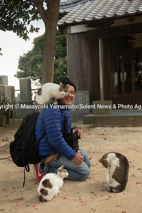 Pictured:  Masayoshi Yamamoto with some of the stray cats<br /> <br /> Leaping cats are pictured in hilarious poses as they play with a photographer.  The excitable felines spring up in the air with their arms outstretched as they try and play with a toy.<br /> <br /> 41 year old Japanese photographer Masayoshi Yamamoto travels around his home country taking pictures of stray cats in these unusual poses.  SEE OUR COPY FOR DETAILS.<br /> <br /> Please byline: Masayoshi Yamamoto/Solent News<br /> <br /> © Masayoshi Yamamoto/Solent News & Photo Agency<br /> UK +44 (0) 2380 458800