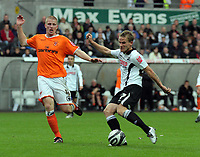 ATTENTION SPORTS PICTURE DESK<br /> Pictured: Mark Gower of Swansea (R) shoots off target while closely marked by Keith Southern of Blackpool (L).<br /> Re: Coca Cola Championship, Swansea City Football Club v Blackpool at the Liberty Stadium, Swansea, south Wales. Saturday 24 October 2009