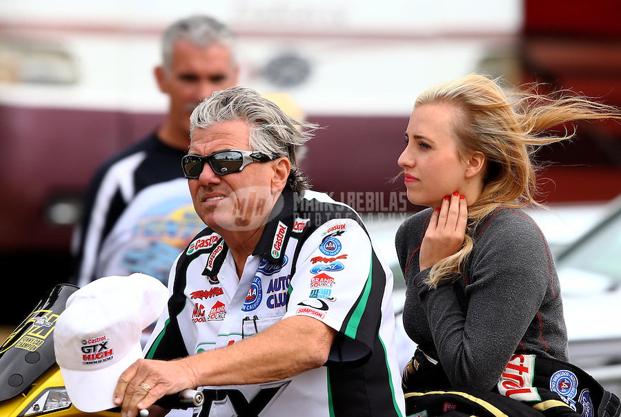 Aug. 3, 2013; Kent, WA, USA: NHRA funny car driver John Force (left) on his scooter with daughter Brittany Force during qualifying for the Northwest Nationals at Pacific Raceways. Mandatory Credit: Mark J. Rebilas-USA TODAY Sports