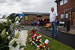 """© Joel Goodman - 07973 332324 . 28/08/2015 . Salford , UK . Paul Massey's brother JOHN MASSEY looks at flowers and tributes , left on Sedan Close in Salford , from where the procession sets off . The funeral of Paul Massey at St Paul's CE Church in Salford . Massey , known as Salford's """" Mr Big """" , was shot dead at his home in Salford last month . Photo credit : Joel Goodman"""