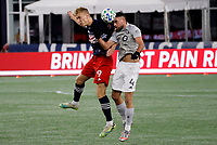 20th November 2020; Foxborough, MA, USA;  Montreal Impact defender Rudy Camacho heads the ball away from New England Revolution forward Adam Buksa during the MLS Cup Play-In game between the New England Revolution and the Montreal Impact