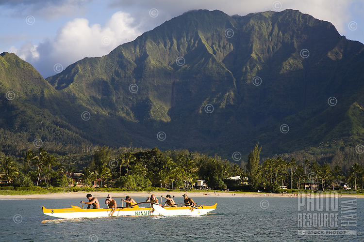 Local Kauaians paddling an outrigger canoe in Hanalei Bay, with Namolokama Mountain in the background