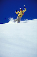 Skier makes a telemark turn on an open powder slope in Mineral Basin on a sunny, clear day. sports, skiing, male, man, men. Ray Nelson. Utah, Wasatch Mountains.