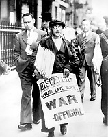 """Newspaper man holding stack of newspapers and sign stating """"Special late news: War - Official,"""" Whitehall, London.<br /> 7 September 1939"""