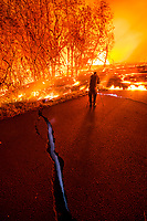 June 2018: A man takes photos of the Kilauea Volcano eruption while standing near a pavement crack that emits blue methane gas, Leilani Estates, Puna, Big Island of Hawai'i.