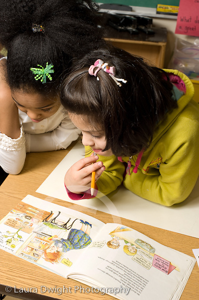 Education Elementary School Grade 2 science social studies project two girls working together looking at Magic School Bus book for information vertical